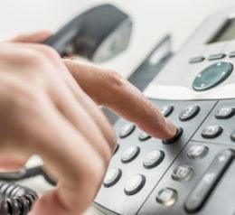 Hand wählt Telefonnummer auf dem Ziffernblock eines Telefons